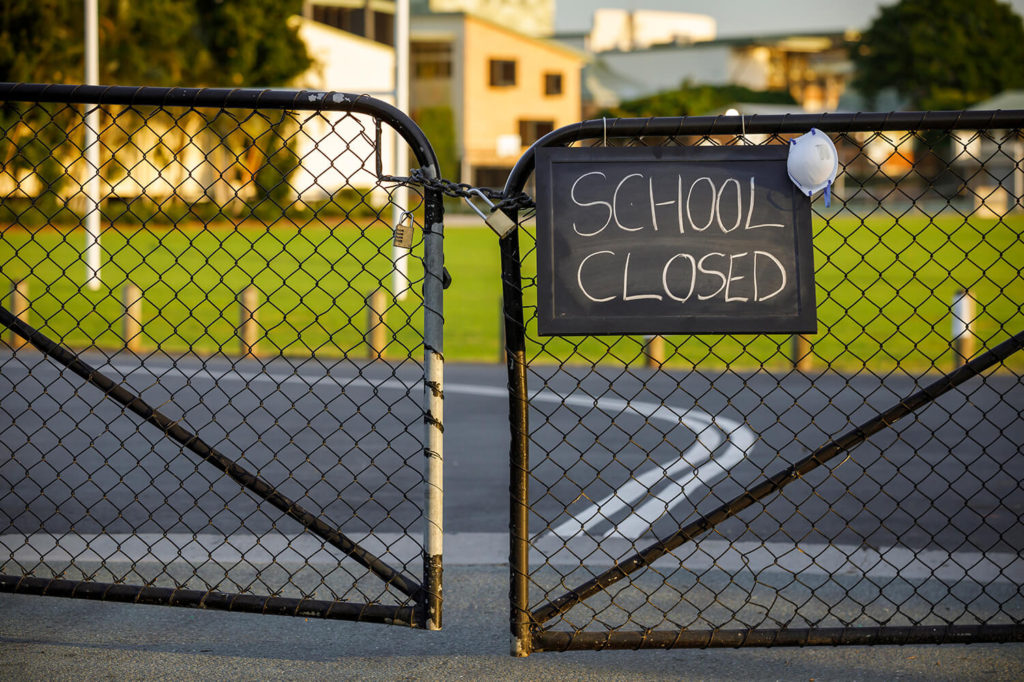 School Closed sign on a locked gate